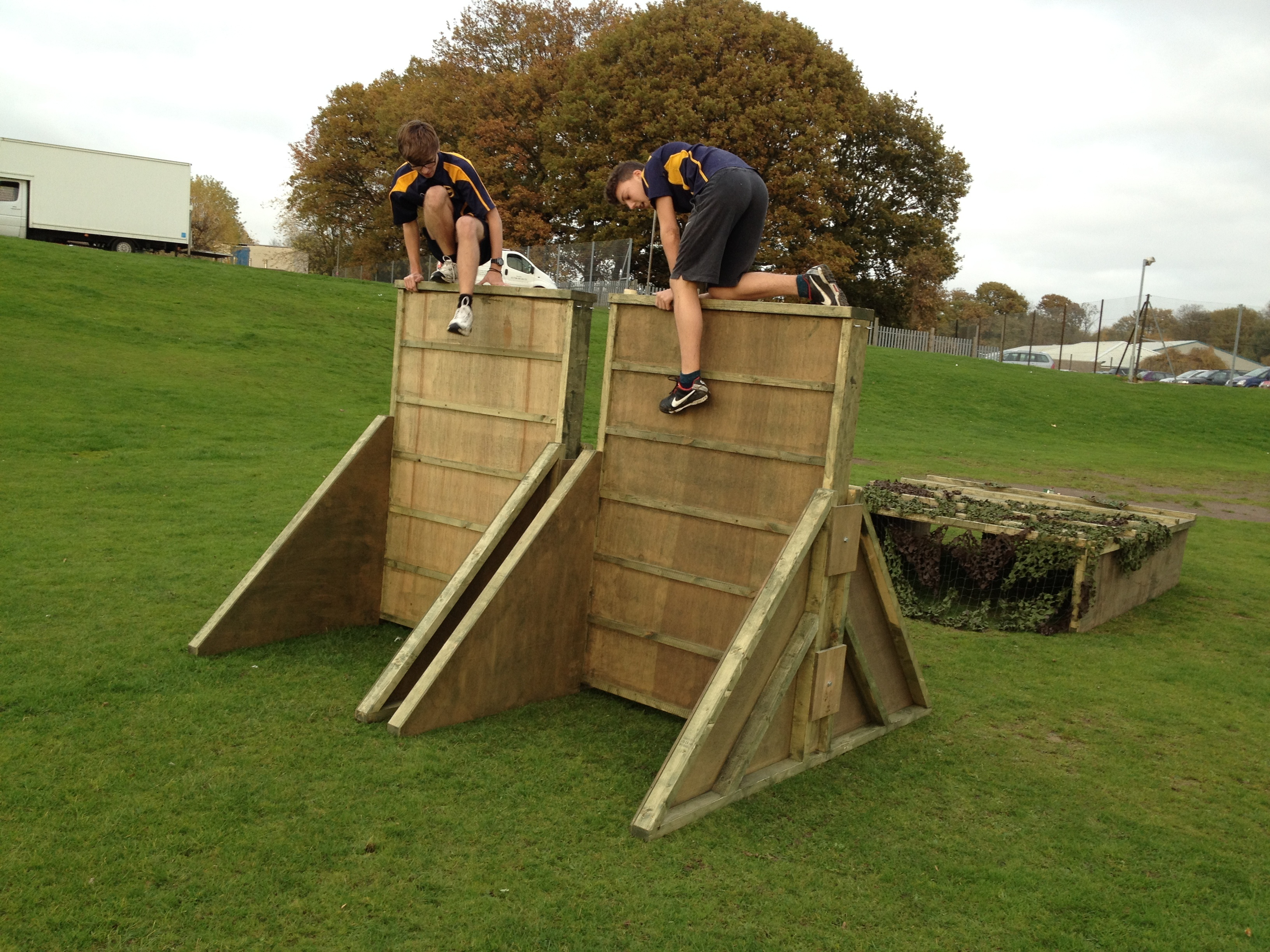 Children Climbing Over Obstacle Course Wall