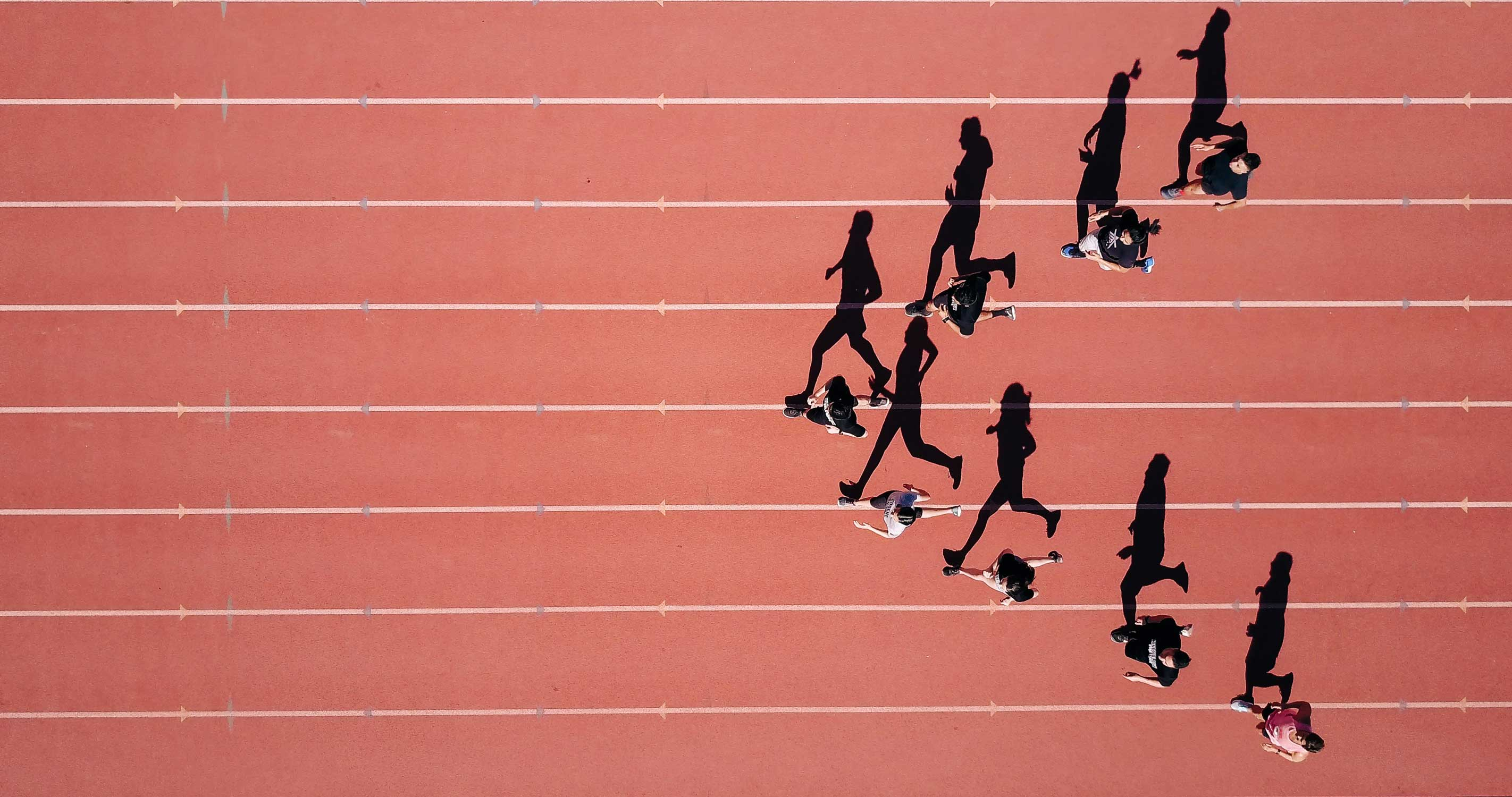 people running on a track from a birds eye view